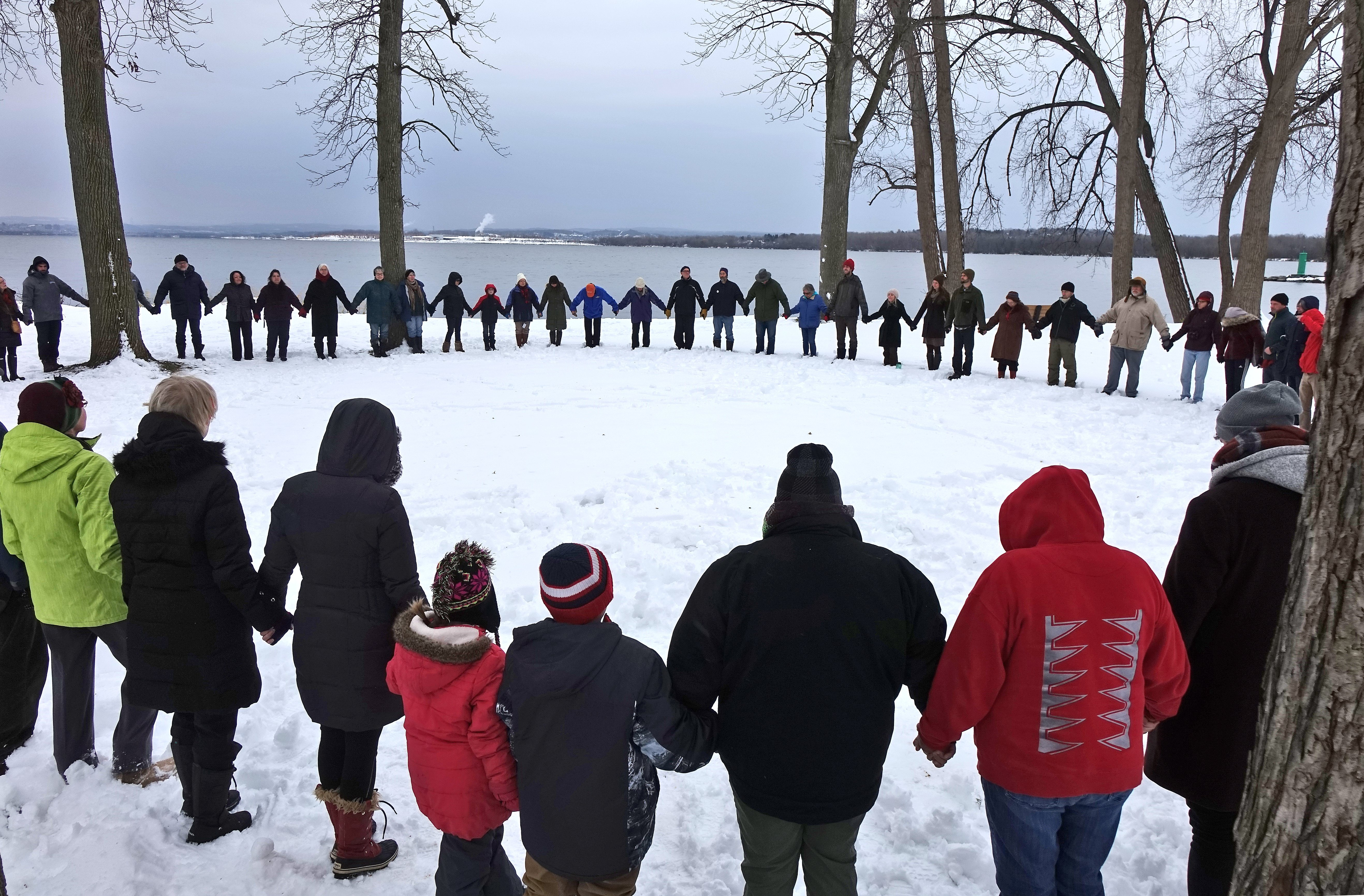Around 90 people join hands in a minute of silence during a Thanksgiving Circle of Peace and Hope held near the shore of Onondaga Lake at Willow Bay in Onondaga Lake Park Thursday morning.  The event was organized by Neighbors of the Onondaga Nation.  November 24, 2016.  Michael Greenlar | mgreenlar@syracuse.com SYR
