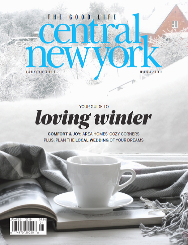 Central New York Magazine January February cover with steaming mug and a book in front of a window overlooking a snowy landscape
