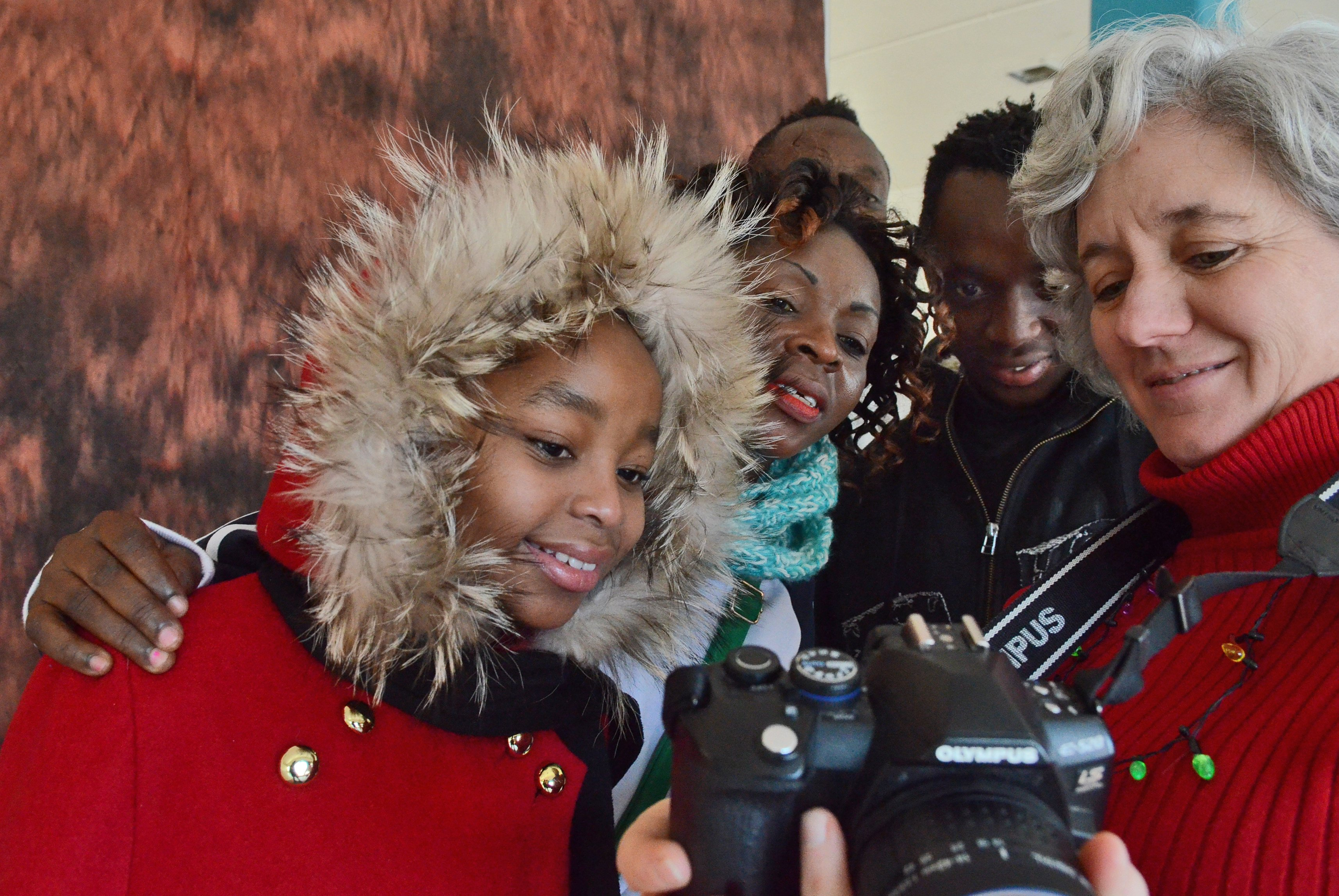 A Congolese family look at their photos, taken by Kate Holmes.  Refugee photo day at Northside CYO on N. Salina St. in Syracuse, presented by Catholic Charities of Onondaga County, January 6, 2017.  Michael Greenlar | mgreenlar@syracuse.com SYR